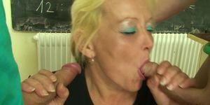 Blonde granny teacher takes two cocks at once